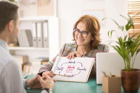 Entrenador sonriente hablando sobre el equilibrio entre la vida laboral y personal con un empleado corporativo