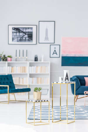 Gold table with plant in bright living room interior with blue armchair and gallery of posters