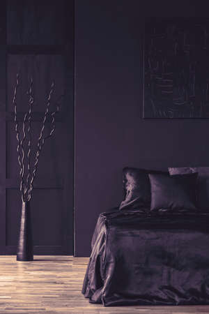 Metal sculpture next to bed with black bedding in monotone bedroom interior