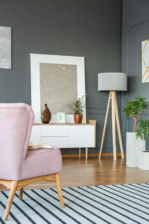 Pink armchair on striped rug in grey living room interior with silver painting on white cupboard