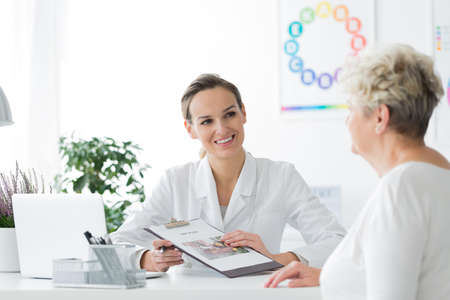 A smiling dietician sitting with her patient and showing her a diet plan