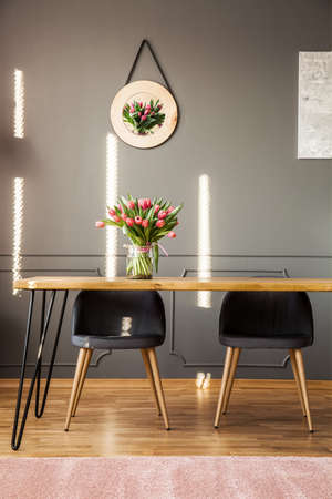 Chairs at wooden table with flowers against grey wall with decor in feminine dining room interior