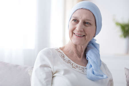 Portrait of a happy, elderly woman in a headscarf for cancer patients, recovering from illness