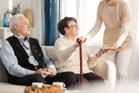 Geriatric couple with arthritis sitting on a couch and being served a piece of cake while waiting for a doctors appointment at a luxury private clinic
