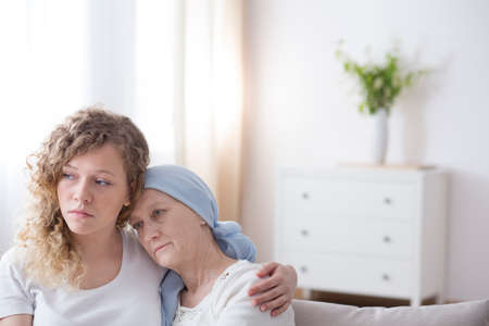Portrait of a sad girl holding an arm around her mom sick with cancer in a simple, white interior Stok Fotoğraf