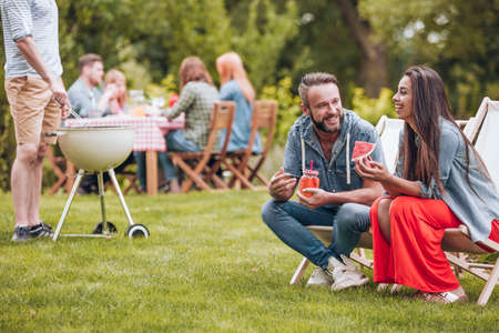 Smiling woman eating watermelon and her friend drinking a cocktail in the garden during a party