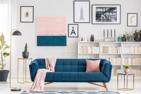 Pink blanket on navy blue sofa in modern living room interior with gallery of posters on the wall Stok Fotoğraf