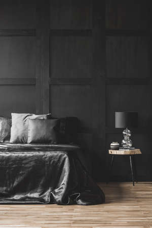 Lamp on wooden table next to bed in modern black bedroom interior with molding on the wall 版權商用圖片