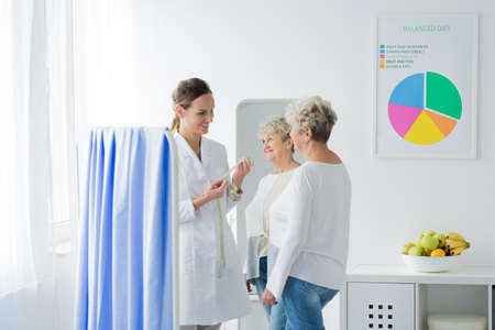 A doctor standing in her office with measuring tape and a patient in front of her. Losing weight concept Stock Photo