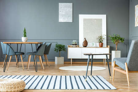 Pouf on striped carpet in grey interior with paintings, chair at dining table and bonsai tree next to a white cupboard