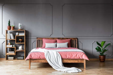 Bright blanket on pink bedding of wooden bed in grey bedroom interior with plant