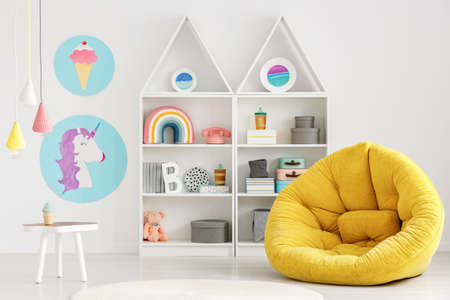 Yellow pouf in colorful scandi kids room interior with posters and lamps above white table