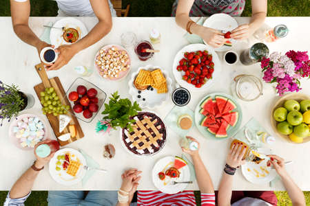 Students having fun at a picnic, eating apples, watermelon, strawberries, grapes, cheese and waffles at a table with a candle and flowers