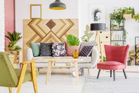 Armchairs, sofa with patterned cushions and wooden wall in a living room interior
