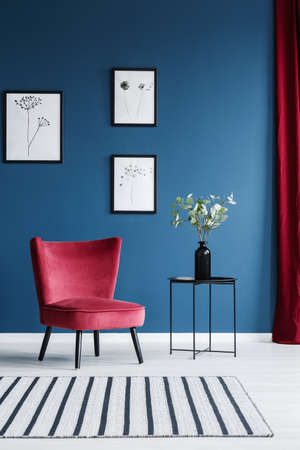 Red armchair, patterned rug, flower in a vase and paintings on the blue wall in living room interior 写真素材 - 101345080