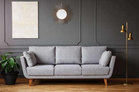 Dekoracyjne lustro i nowoczesny obraz wiszący na ścianie z sztukaterią w ciemnoszarym wnętrzu salonu ze świeżą rośliną, złotą lampą i jasną sofą
