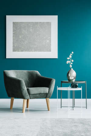 Painting on a turquoise wall, grey armchair and side tables in a waiting room interior Stock Photo