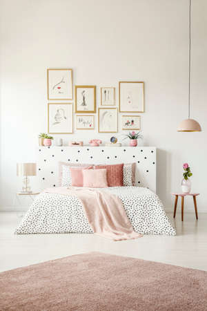 Pink rug and posters in woman's bedroom interior with flower on table next to patterned bed