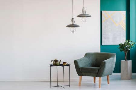 Elegante interior en blanco y verde con sillón y tetera sobre la mesa, lámparas modernas, una planta en una maceta y un cartel.