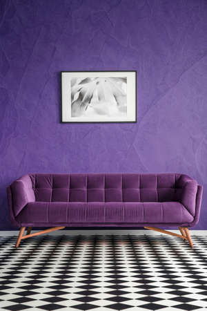 Poster on violet wall above suede sofa in living room interior with checkerboard floor Reklamní fotografie