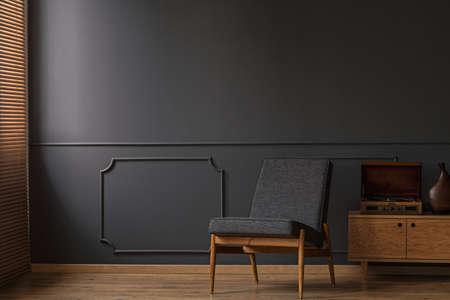 Grijze fauteuil op de grijze lege muur met lijstwerk in woonkamer interieur met houten vloer