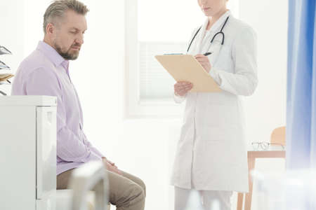 Sick man sitting next to a urologist in white uniform with stethoscope while making a diagnosis