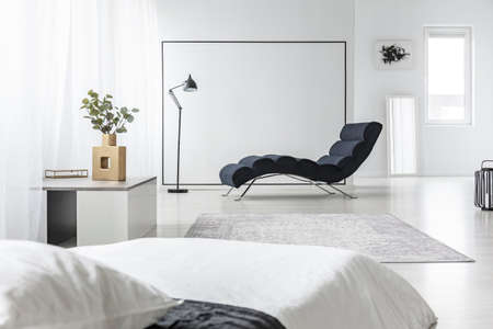 Lamp next to black chaise lounge in open space interior with white bed and plant on a table