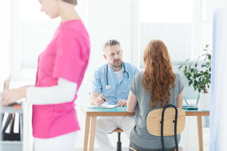 Sick woman talking to a gynecologist about her disease in the clinic Stock Photo