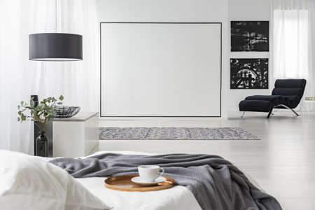 Grey blanket on white bed in bedroom interior with chaise lounge against the wall with black paintings