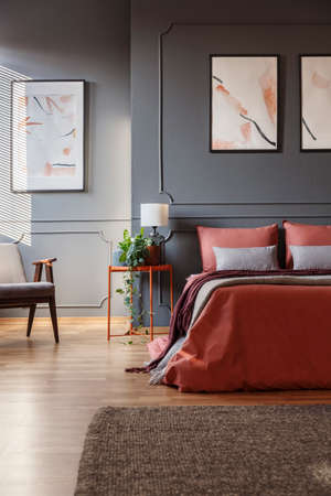 Orange bed against dark wall with molding and white posters next to a metal bedside table with a lamp on it in bedroom interior. Real photo