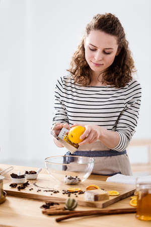 Woman grating the skin of an lemon while making vegan soap