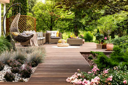 Beautiful wooden terrace with garden furniture surrounded by greenery on a warm, summer day