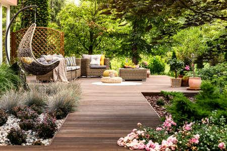 Schöne Holzterrasse mit Gartenmöbeln, umgeben von viel Grün an einem warmen Sommertag