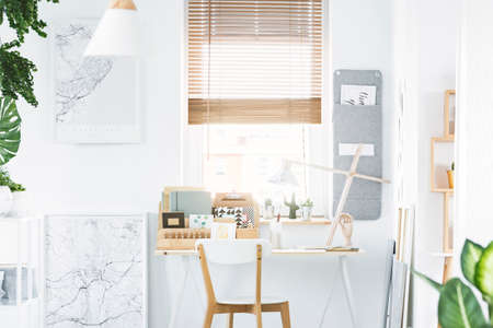Wooden chair at desk with white lamp in home office interior with window and maps