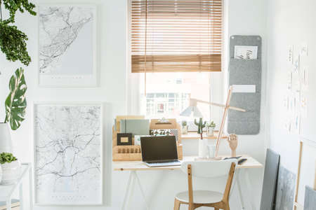 Wooden chair at desk with laptop in freelancers interior with window and maps on white wall 版權商用圖片