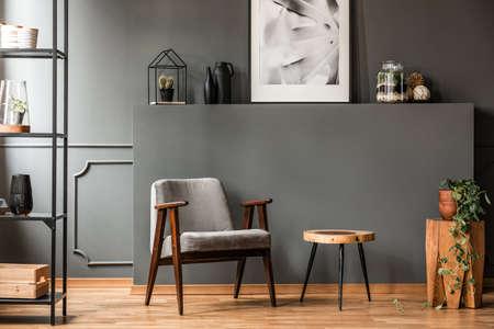 Szary fotel przy drewnianym stole we wnętrzu salonu z rośliną i plakatem