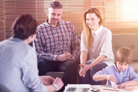 Praten met de leraar van hun zoon en gelukkige familie op kantoor Stockfoto