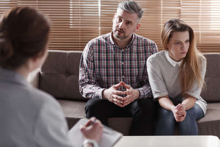 Depressed woman and husband talking with therapist for couples Stock Photo