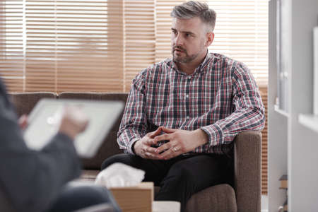 Worried man consulting on a marital problem during therapy with a counselor Stock Photo