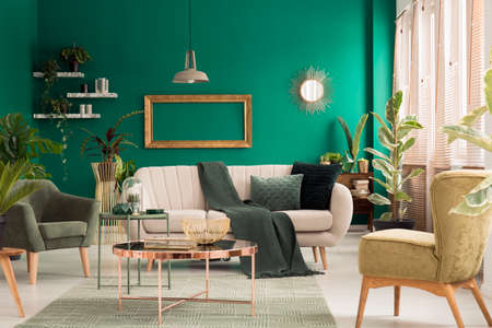 Green blanket thrown on bright sofa with pillows standing in living room interior with fresh plants and mockup frame on the wall