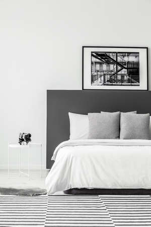 Black poster on grey bedhead of bed in minimal hotel room interior with white table