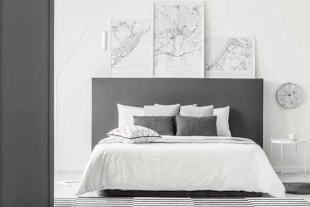 Maps above bed with grey bedhead and pillows in simple bedroom interior with clock