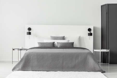 Bed with grey bedding between silver and white table in bedroom interior with screen Stockfoto