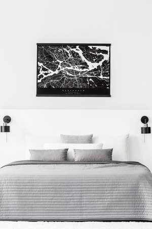 Black map on white wall above bed with grey cushions and blanket in contrast bedroom interior