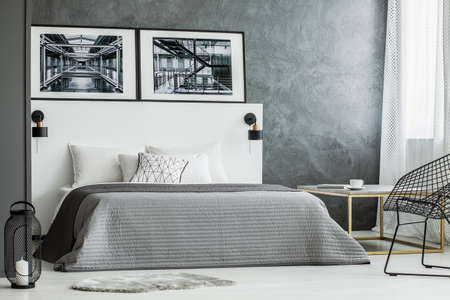 Posters on white bedhead of bed with grey bedding near lantern in bedroom interior with concrete wall 写真素材