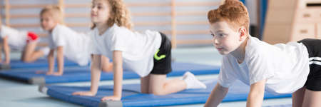 Young boy exercising on a blue mat during corrective gymnastics classes at school