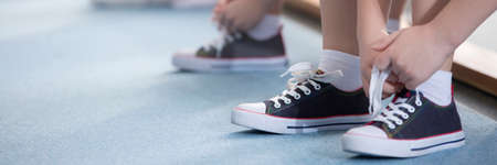 Close-up de niño atando sus zapatos antes de las clases de educación física
