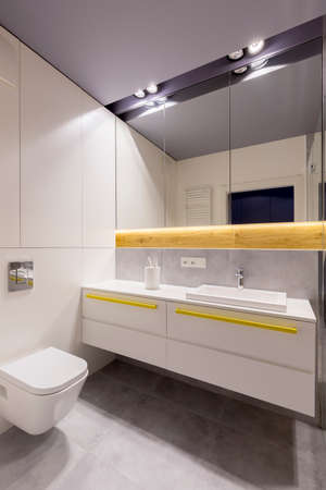 Mirror and lights above washbasin and cabinet with yellow accents in modern bathroom interior