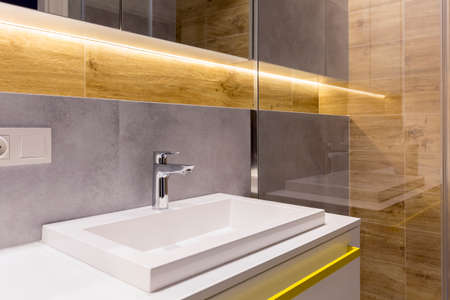 Close-up of washbasin with faucet against grey and wooden wall in elegant bathroom interior Imagens