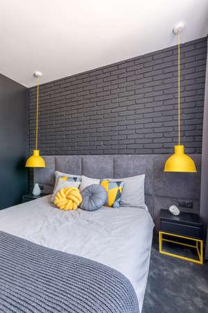 Grey bed between yellow lamps in modern bedroom interior with brick wall  Imagens